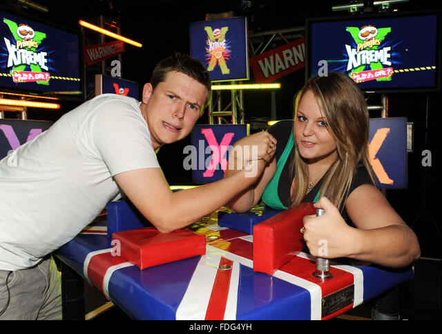 World arm wrestling champion Joanne 'The Hitwoman' Poole shows reporter Jonny Greatrex aka Jonny Dangerous - Stock Image
