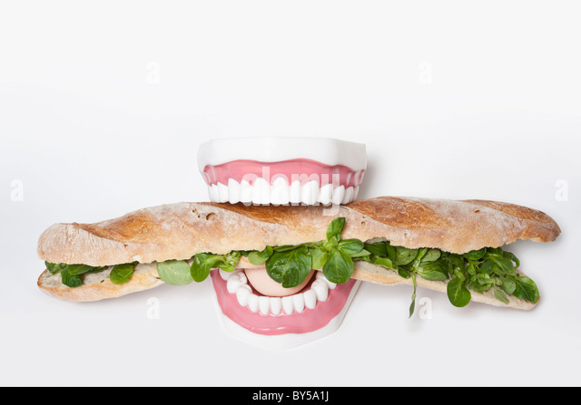 Fake teeth biting into a submarine sandwich - Stock Image