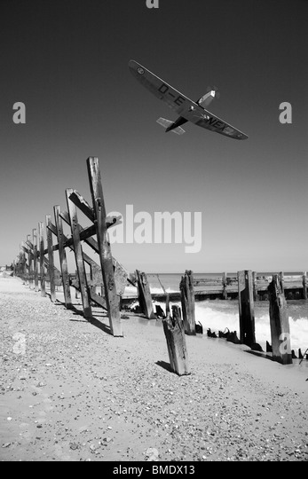 An old small aircraft flying over broken sea defenses. - Stock Image