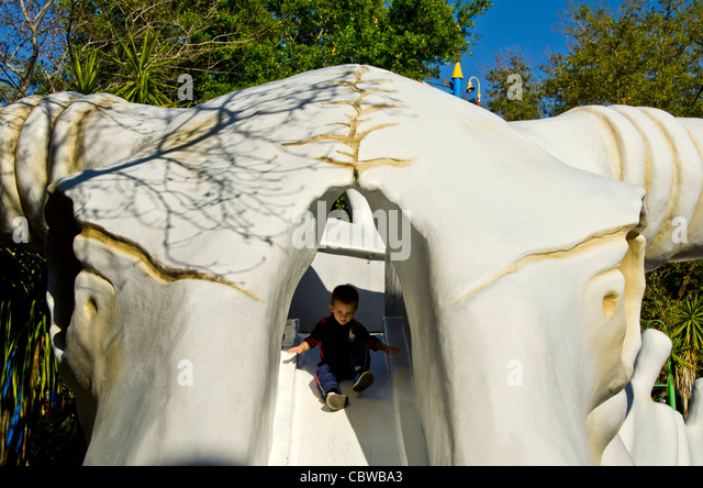 Fivels Playland kids playground with boy sliding down the head of a huge cow skeleton at Universal Studios Orlando - Stock Image