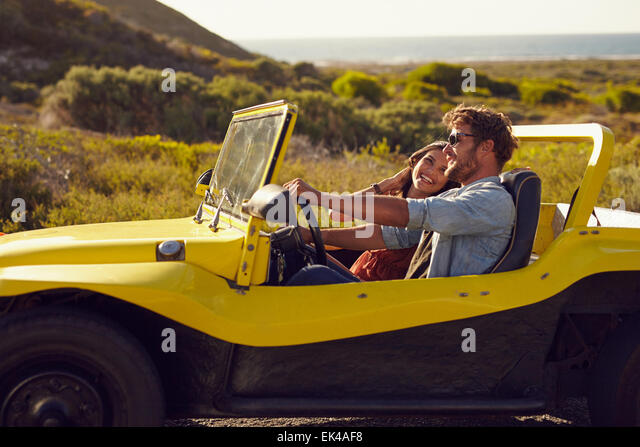Smiling couple going on holidays together on a summer day. Young man with his girlfriend on  road trip in a buggy - Stock-Bilder