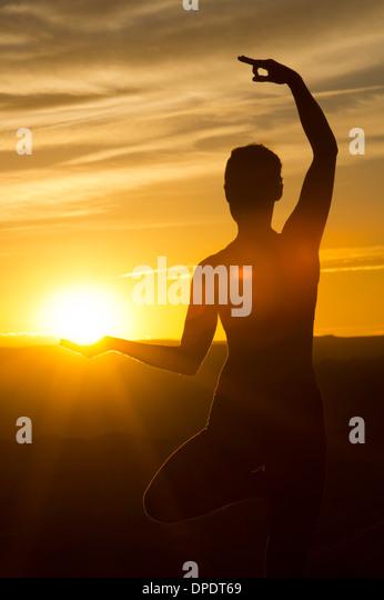 Young woman doing yoga in sunlight, Moab, Utah, USA - Stock Image