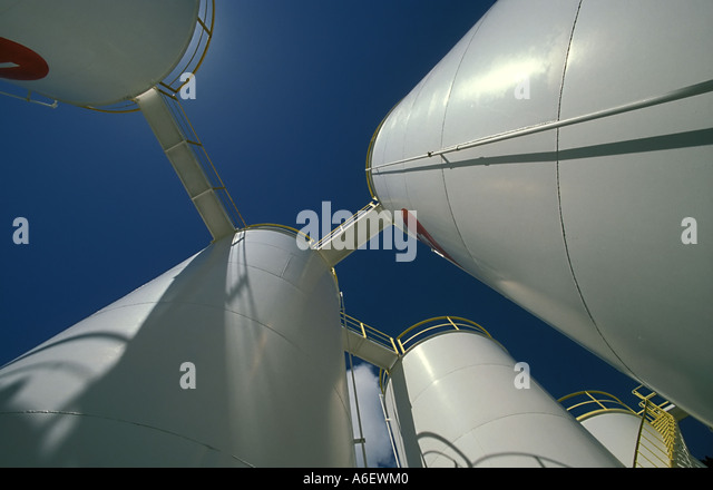 Worms eye view of oil storage tanks against a blue sky - Stock-Bilder