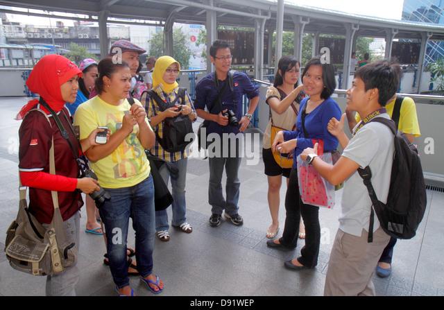 Bangkok Thailand Pathum Wan Phaya Thai Road Skywalk Asian woman man guide explaining Muslim - Stock Image