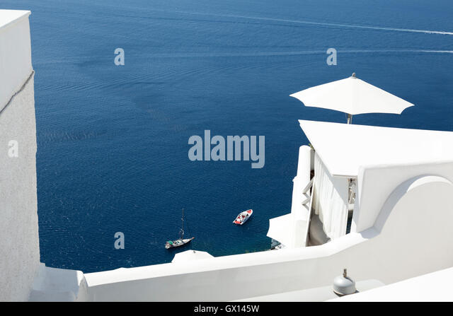 Traditional white painted buildings in Oia, Santorini with the blue ocean in the background. - Stock Image
