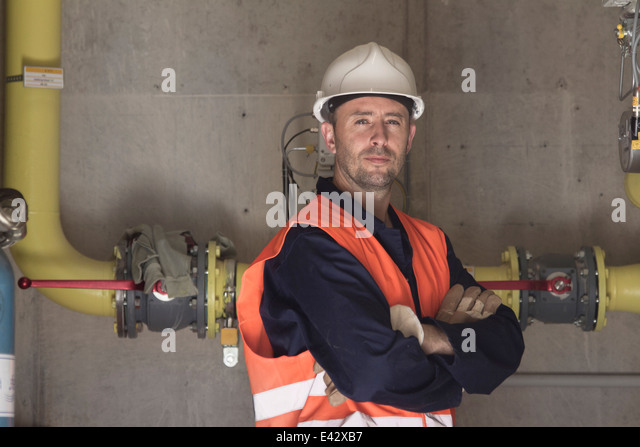 Portrait of technician with arms folded in power station - Stock Image