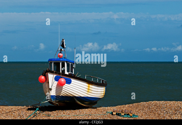 A fishing boat beached on the shingle at Dungeness. - Stock Image