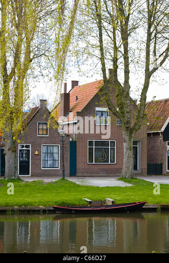 Canal in front of homes in the village of Edam in North Holland, The Netherlands. - Stock Image