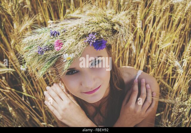 Portrait Of Beautiful Young Woman Wearing Flowers On Head At Field - Stock-Bilder