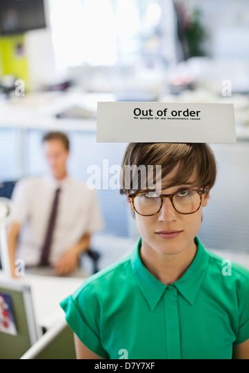 Businesswoman wearing 'out of order' sign - Stock Image