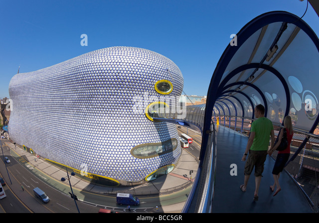 Young man and woman couple walking along skywalk to Selfridges in the Birmingham Bullring West Midlands England - Stock Image