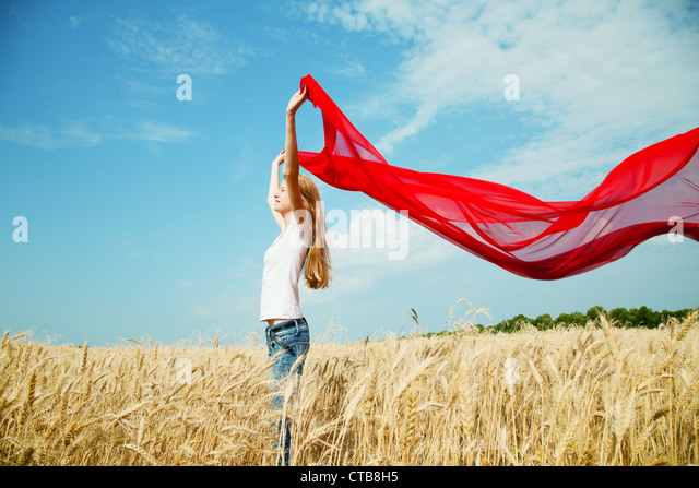 Teen girl at a wheat field with red fabric - Stock Image