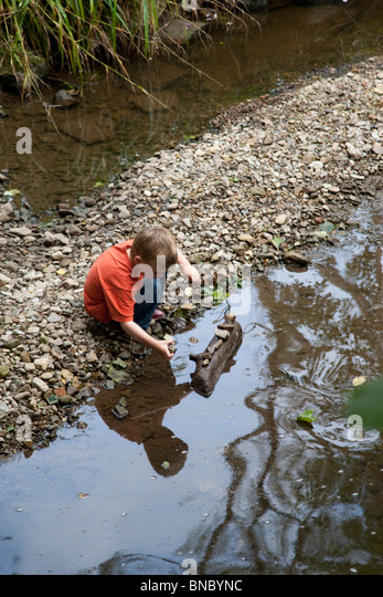 Small boy contemplating stones beside the River Alyn. - Stock Image
