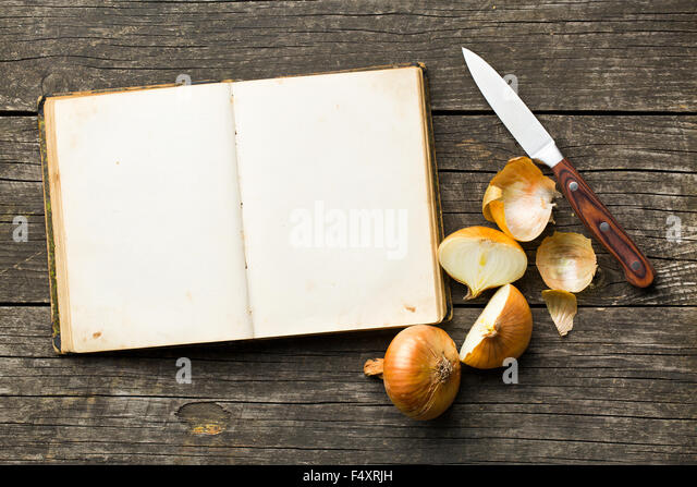 blank recipe book and halved onion - Stock Image