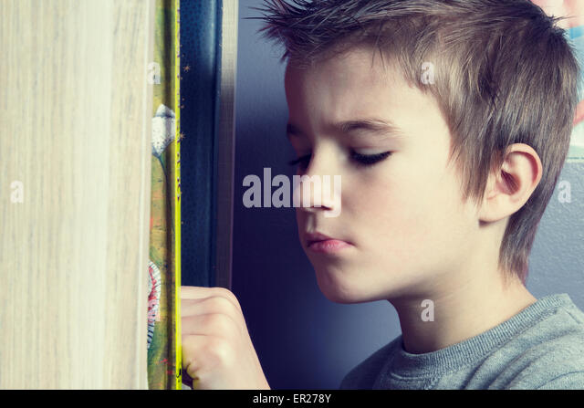 boy 8 years choosing a book in his bedroom - Stock Image