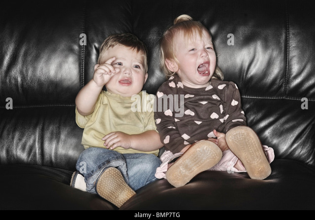 Edmonton, Alberta, Canada; Two Young Children Sitting On The Couch Together And Crying - Stock Image