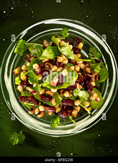 Bean salad, chickpeas, kidney beans, and black eyed beans with spinach, red onion and coriander. - Stock Image