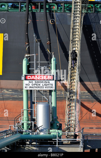 Side of a fuel tanker ship showing hoses for offloading fuel to shore and man climbing long tall wooden ladder to - Stock Image