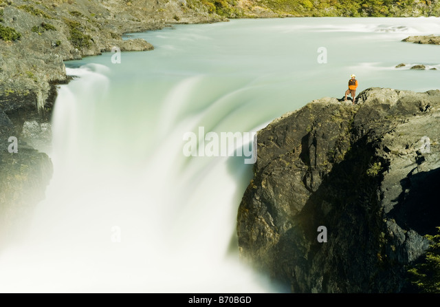 A hiker pauses to look at Salto Grande in Las Torres Del Paine National Park, Chile. - Stock Image