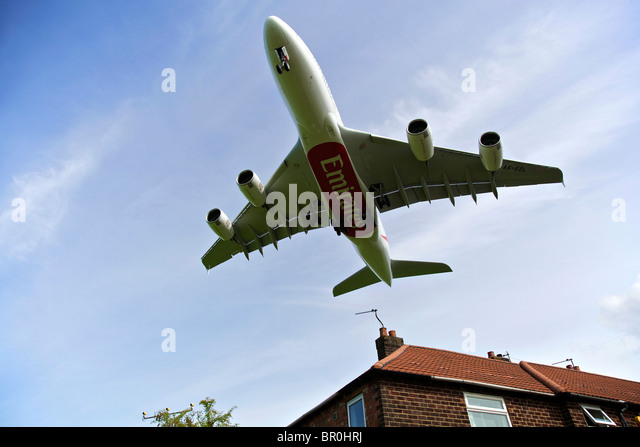 Emirates airline Airbus A380 arrives at Manchester airport, flying low over house rooftop. - Stock Image