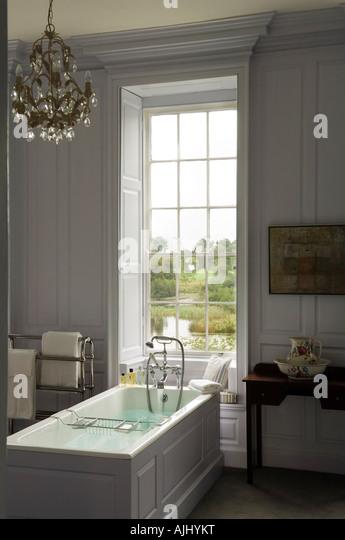 Bathroom with wood panelled walls and chandelier in Irish castle - Stock-Bilder