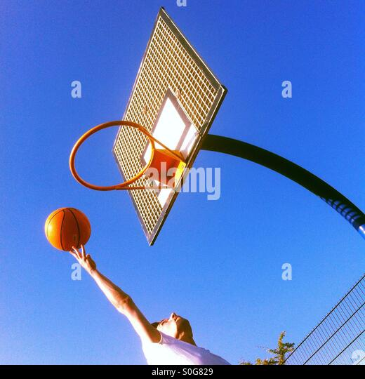 Man throwing a basketball in to the hoop - Stock Image