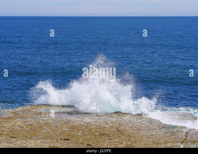 Small wave crashes aginst the rocks at Portland Bill, Dorset, UK - Stock Image