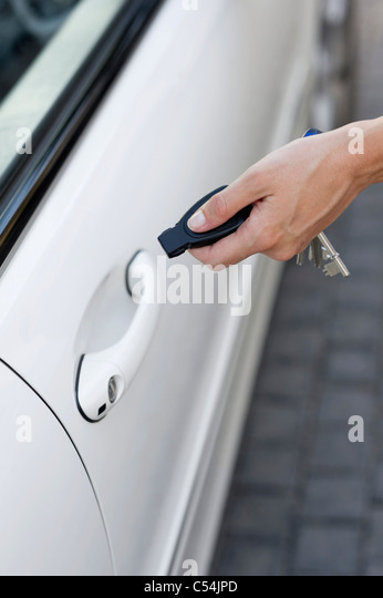 Person's hand unlocking the car with remote control - Stock Image