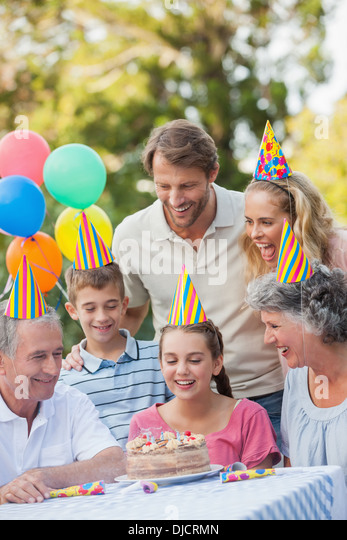 Cheerful family wearing party hat while celebrating birthday - Stock-Bilder