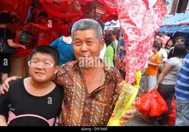 Singapore Chinatown shopping market marketplace Asian man senior boy grandson grandfather family - Stock Image