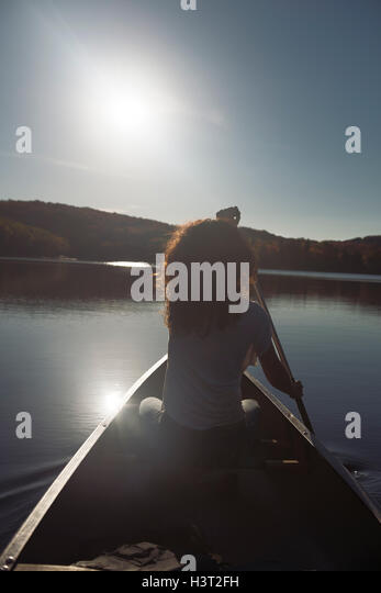 Young woman canoeing on a lake in fall. Arrowhead Provincial Park, Muskoka, Ontario, Canada. - Stock Image