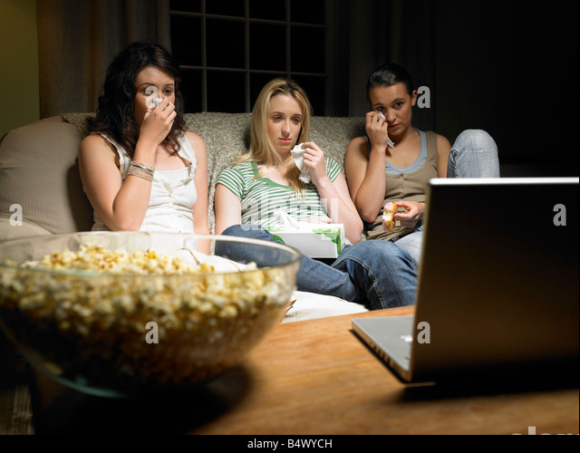 Three young women watching a movie - Stock Image