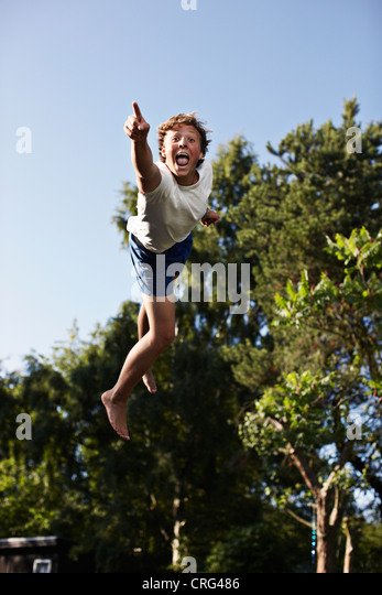 Teenage boy pointing in mid-air - Stock Image