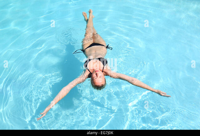 Caucasian lady floating in swimming pool. - Stock Image