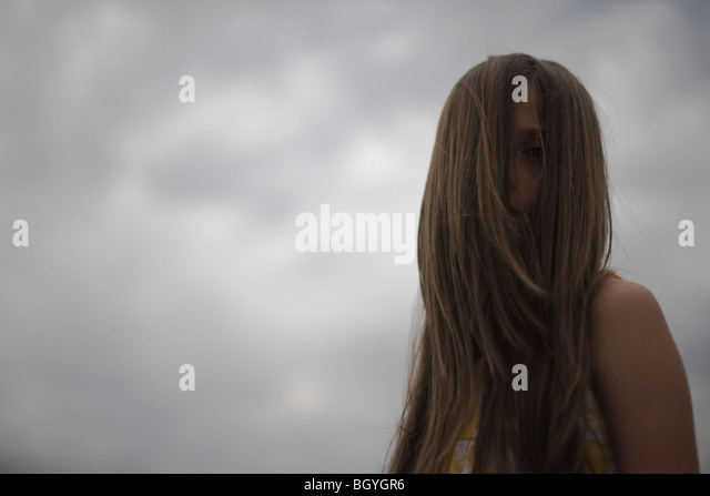 Female with face obscured by long hair - Stock Image