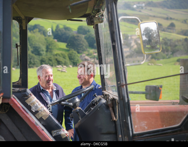 Farmer and son talking next to tractor in field - Stock Image