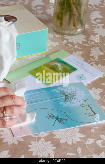 hand holding tissue with Sympathy cards and box of tissues on tablecloth - Stock Image