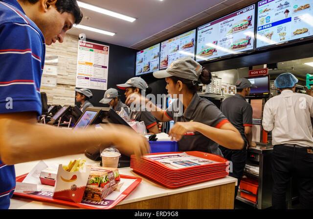 Mumbai India Asian Lower Parel High Street Phoenix mall inside restaurant Burger King fast food counter woman man - Stock Image