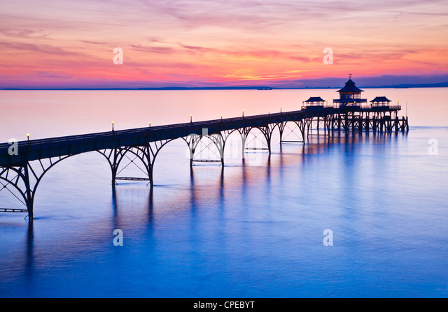 The sun sets over the Bristol Channel behind the Pier at Clevedon, Somerset, England, UK - Stock Image