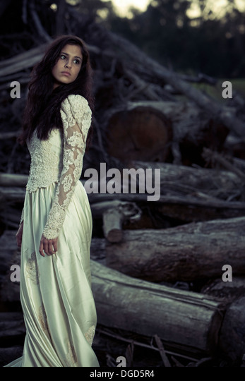 Woman in wedding dress standing in front of cut down trees - Stock-Bilder