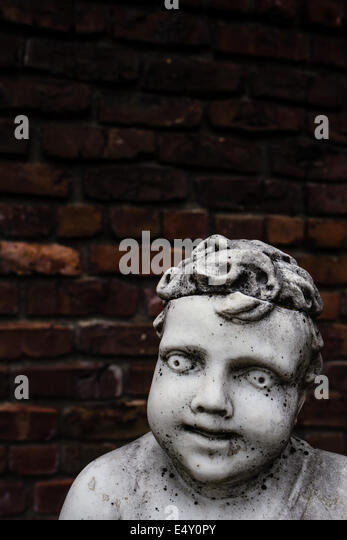 An old creepy vintage marble garden statue of a cherub or boy against and old brick wall.  Copy space above. - Stock Image