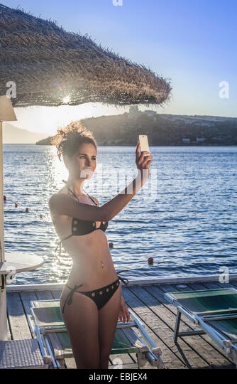 Young woman taking selfie on vacation - Stock Image