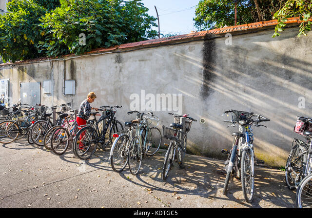 Woman parking her bicycle, La Rochelle, France. - Stock Image