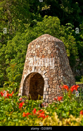 Old sugarmill windmill tower surrounded by trees and red flowers, Montego Bay, Jamaica - Stock Image