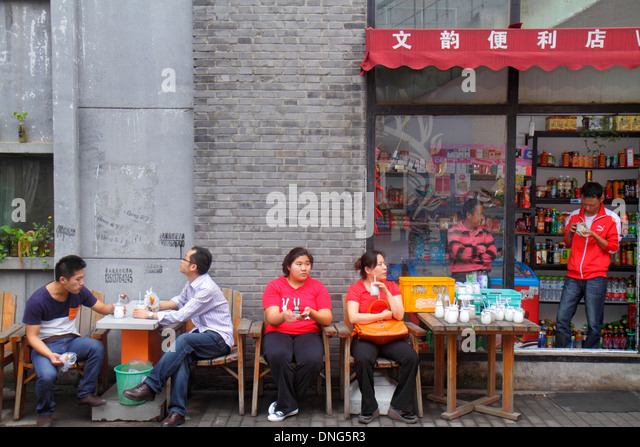 China Beijing Chaoyang District convenience store front entrance tables Asian woman man Chinese characters hànzì - Stock Image