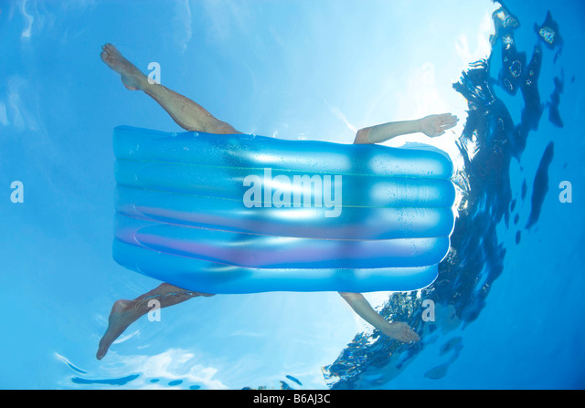 Man on inflatable lilo in pool - Stock Image