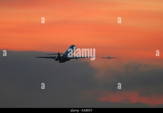 Two commercial airplanes climbing out after take off - Stock Image