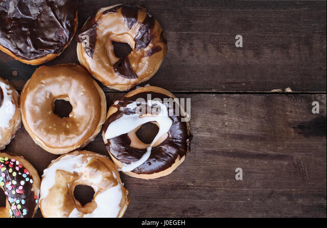 Background of chocolate, carmel, glazed and filled donuts over a rustic background with copy space. Image shot from - Stock Image