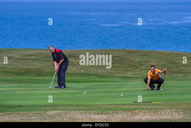 Putting on a seaside golf course. - Stock Image