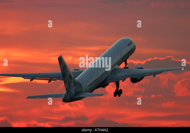 British Airways commercial airplane Boeing 757 and dramatic red sunset in the background - Stock Image